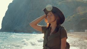 Portrait of a beautiful red-haired traveler girl in a cowboy hat on the sea beach. Slow motion stock video