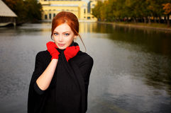Portrait of a beautiful red-haired woman. In red gloves Stock Image