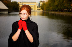 Portrait of a beautiful red-haired woman. In red gloves Royalty Free Stock Photos