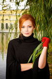 Portrait of a beautiful red-haired woman. In red gloves Royalty Free Stock Photography