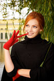 Portrait of a beautiful red-haired woman. In red gloves Stock Images