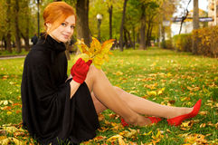 Portrait of a beautiful red-haired woman. In red gloves sitting on the grass Stock Images