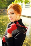 Portrait of a beautiful red-haired woman. In red gloves Stock Photography