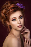 Portrait of beautiful red haired woman with purple hair-slide. Portrait of beautiful red-haired woman with purple hair-slide looking straight to camera and Royalty Free Stock Photography