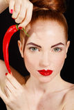 Portrait of beautiful red-haired woman with red hot spicy cayenne chili pepper Stock Image