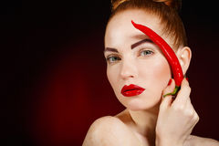 Portrait of beautiful red-haired woman with red hot spicy cayenne chili pepper Royalty Free Stock Images