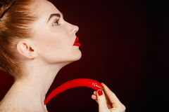 Portrait of beautiful red-haired woman with red hot spicy cayenne chili pepper. Beautiful seductive woman fashion girl with red lips holding a red chili pepper stock image