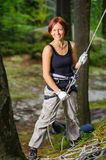 Portrait of beautiful red-haired woman rock climber. Belaying another climber with rope. Summer time. Climbing equipment Royalty Free Stock Images