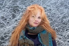 Portrait of a beautiful red-haired woman with scarf, with long curly hair enjoys nature`s cold in winter, standing in front of a royalty free stock photo