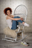 Portrait. Of a beautiful red-haired young girl on a rocking chair Stock Photo