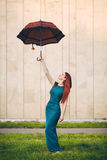 Portrait of a beautiful red-haired young woman with an umbrella. Portrait of a beautiful red-haired young woman in a green dress with an umbrella Stock Photography