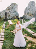 Portrait of beautiful redhair bride posing near rocks. Honeymoon at Carpathians in Tustan fortress Royalty Free Stock Photos