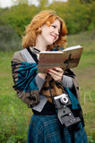 Portrait of a beautiful redhair girl in the autumn park. Royalty Free Stock Images