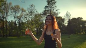 Portrait of beautiful redhair young woman. Blow bubble in the park. Portrait of beautiful redhair young woman. Blow bubbles in park. Super slow motion shot in stock footage