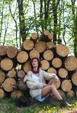 Portrait of beautiful redhaired girl in a fur coat sitting on logs Royalty Free Stock Image