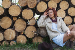 Portrait of beautiful redhaired girl in a fur coat sitting on logs Royalty Free Stock Photos