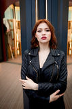 Portrait of a beautiful redhead.Fiery hair and full lips. Walking around the city Royalty Free Stock Images