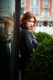 Portrait of a beautiful redhead.Fiery hair and full lips. Walking around the city Stock Photos