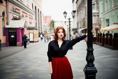 Portrait of a beautiful redhead.Fiery hair and full lips. Walking around the city Royalty Free Stock Photography