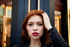 Portrait of a beautiful redhead.Fiery hair and full lips. Walking around the city Royalty Free Stock Image