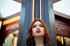 Portrait of a beautiful redhead.Fiery hair and full lips. Walking around the city Stock Photo