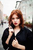 Portrait of a beautiful redhead.Fiery hair and full lips. Walking around the city Stock Image