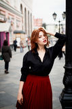 Portrait of a beautiful redhead.Fiery hair and full lips. Walking around the city Royalty Free Stock Photos