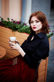 Portrait of a beautiful redhead.Fiery hair and full lips. Walking around the city Stock Photography