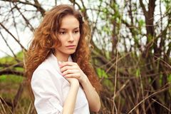 Portrait of a beautiful redhead girl. In spring garden Stock Photo