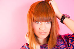 Portrait of beautiful redhead girl near wall. Royalty Free Stock Photography