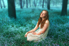 Portrait of beautiful redhead girl sitting on the meadow with forget-me-not flowers. Portrait of beautiful girl sitting on the meadow with blue flowers. Colorful Royalty Free Stock Photo