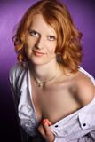 Redhead in a open white shirt on a violet background Stock Photos
