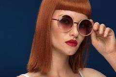 Beautiful redhead girl in sunglasses on blue background. Stock Photos