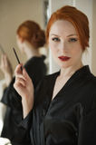 Portrait of a beautiful redheaded woman in robe holding a lip liner Royalty Free Stock Photo