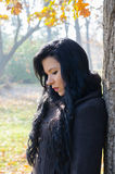 Portrait of beautiful sad girl in sunny autumn forest. Portrait of the beautiful sad girl in forest on sunny autumn day royalty free stock photo