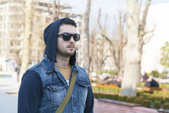 Portrait of beautiful sad young man on the street. Portrait of beautiful serious young man with jacket and hood stock photography