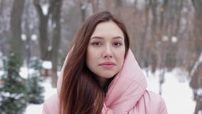 Portrait of a beautiful and satisfied woman with brown hair, nodding agreement. Which means yes, against a winter park or forest background. Concept of emotion stock video footage