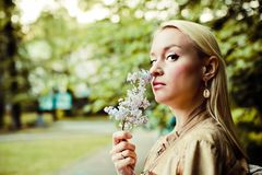 Young blonde woman inhales the scent of flowers and looks at you royalty free stock photography