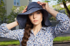 Scared girl keeping her hat with hands. Portrait of a beautiful scared young woman in a hat keeping her head with hands, outdoors Stock Photo