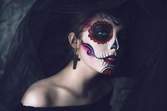 Portrait of a sugar skull. Portrait of a beautiful and scary Calavera Catrina in black dress and black hat with a veil over dark background. Sugar skull makeup royalty free stock photography