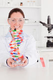 Portrait of a beautiful scientist showing the dna Stock Photography