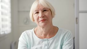 Portrait of beautiful senior blond woman at home. Sitting in white living room looking at camera stock video footage