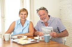 Portrait of a beautiful senior couple having breakfast together. Portrait of a attractive mature retired couple having breakfast together at home enjoying the Stock Photo