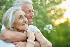 Portrait of beautiful senior couple hugging in the park royalty free stock photo