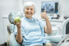 Portrait of a senior woman at the dental office. Portrait of a beautiful senior woman with healthy smile holding green apple at the dental office stock images