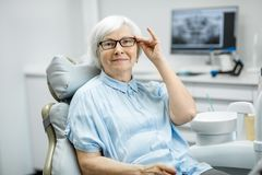 Portrait of a senior woman at the dental office. Portrait of a beautiful senior woman with healthy smile sitting at the dental office stock images
