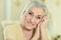 Beautiful senior woman with jewelry posing at home