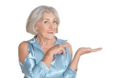 Portrait of beautiful senior woman in light blue blouse pointing to the right. Isolated on white background stock photography