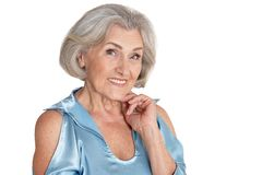 Portrait of beautiful senior woman in light blue blouse posing isolated. On white background stock images