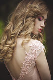 Portrait of a beautiful sensual blonde with protective eyes from the back. Girl with beautiful lips. Dress with neckline royalty free stock images